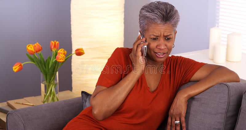 African grandmother talking on smartphone. Happy African grandmother talking on smartphone stock photography