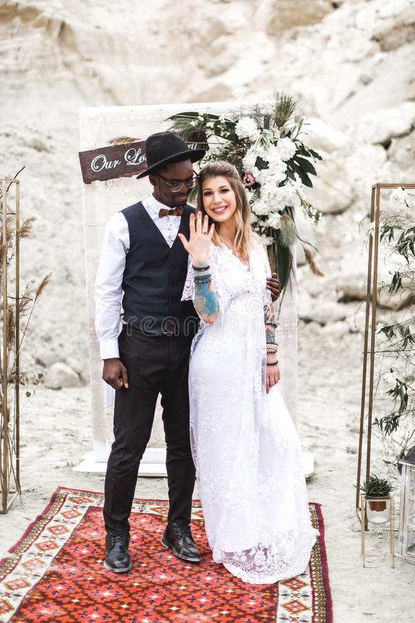 African groom and Caucasian bride embracing each other in a boho style before the wedding arch from fresh flowers. Bride. Is showing her wedding ring, smiles royalty free stock photo
