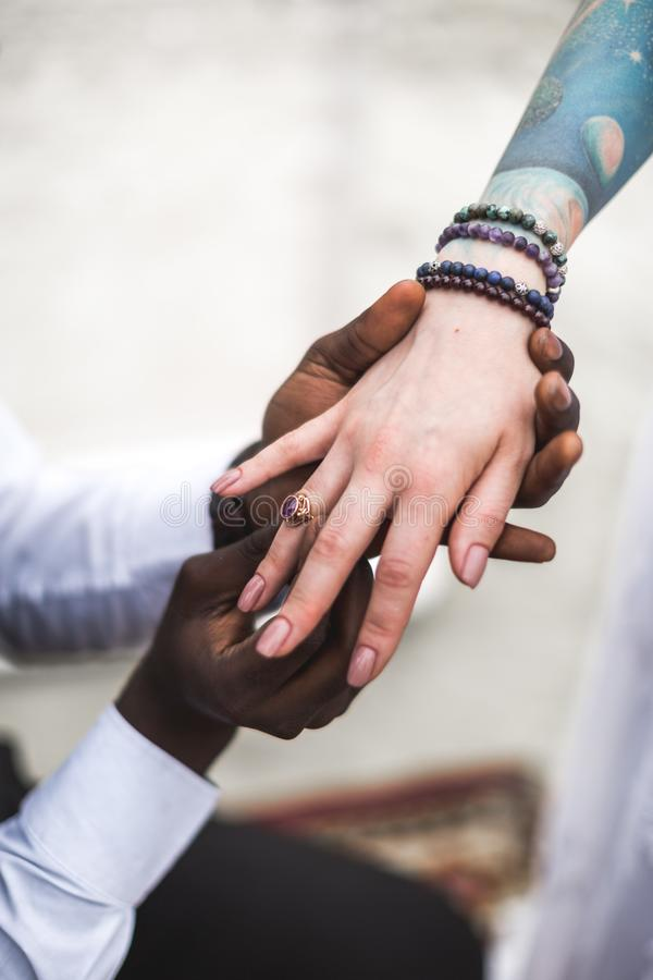 African groom wears wedding ring on the finger of Caucasian bride. Marriage closeup. boho wedding. boho style. happy royalty free stock image