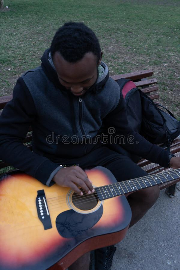 African guy with an acoustic guitar in a suitcase getting ready to play in the park stock photo