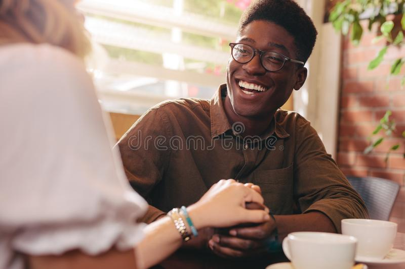 Cheerful couple in love sitting at a coffee shop royalty free stock photography