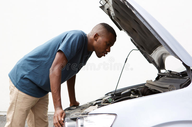 African guy looking under the hood of his broken down car stock photo