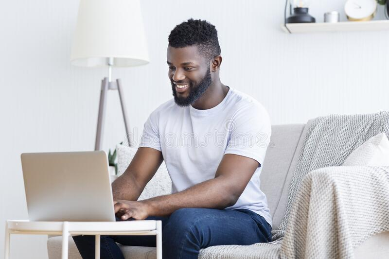 African guy playing video game on laptop at home royalty free stock photo