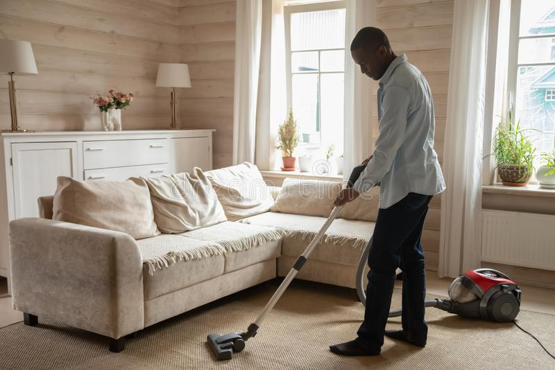 African guy use vacuum cleaner cleaning carpet in living room stock photos