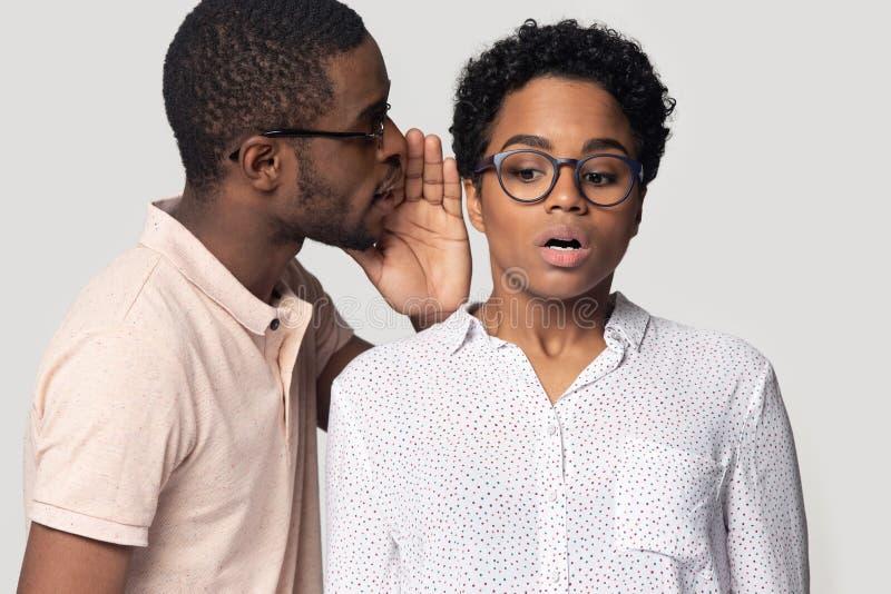 African guy whispering to ear of girl secret, studio shot royalty free stock images