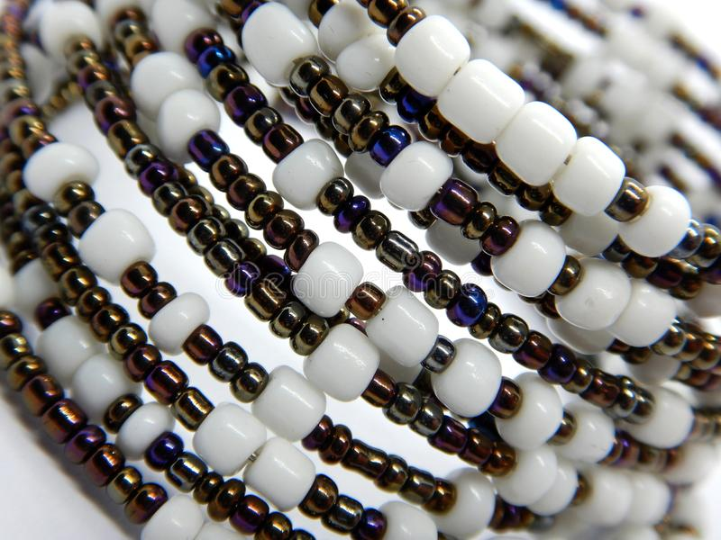 African handmade bead bracelet macro. White and metal bead-spiral royalty free stock image