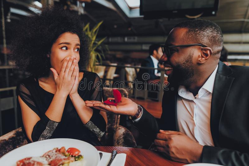 African Handsome Man Proposing to Girlfriend. Romantic Couple in Love Dating. Cutel Man and Girl in a Restaurant. Romantic Concept. Surprised Attractive Woman stock image