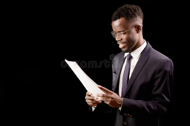 African happy student wearing stylish suit reading a report stock photo