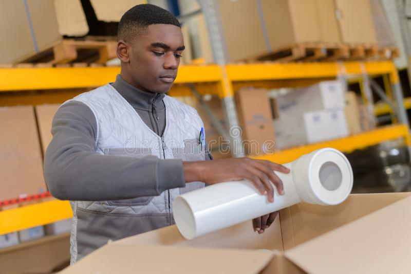 African hardware store worker shipping plastic pipe stock photos