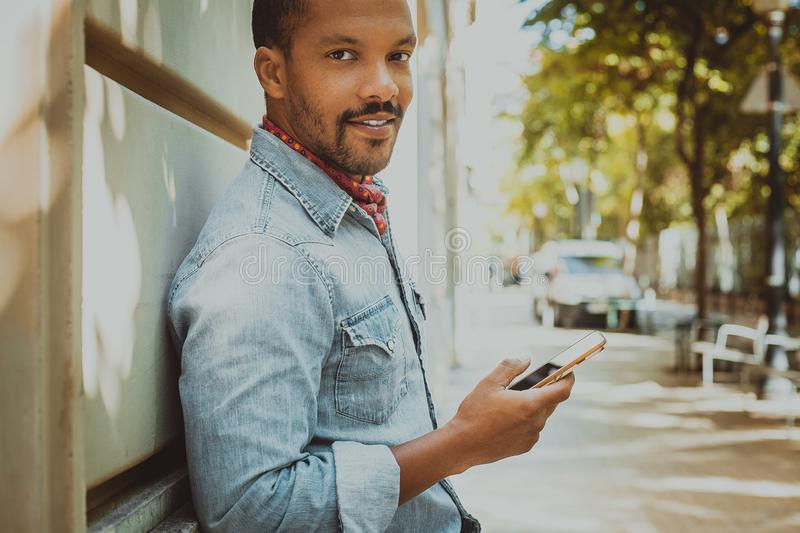 African hipster holding smartphone browsing internet and checking news feed on social media.Man using cell phone.  stock photos