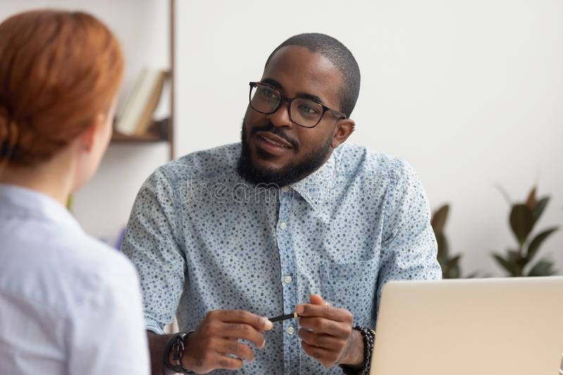 African hr manager listening to caucasian applicant at job interview. African hr manager listening to caucasian female applicant asking questions at job royalty free stock photography