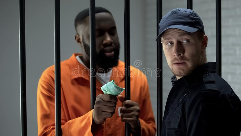 African imprisoned criminal giving euro bills to prison guard, faulty system. Stock photo royalty free stock image
