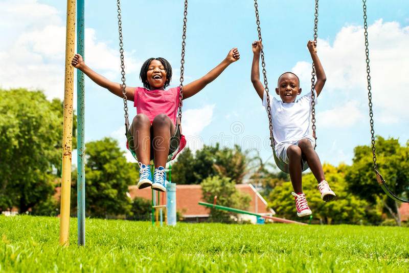 African kids playing on swing in neighborhood. stock photography