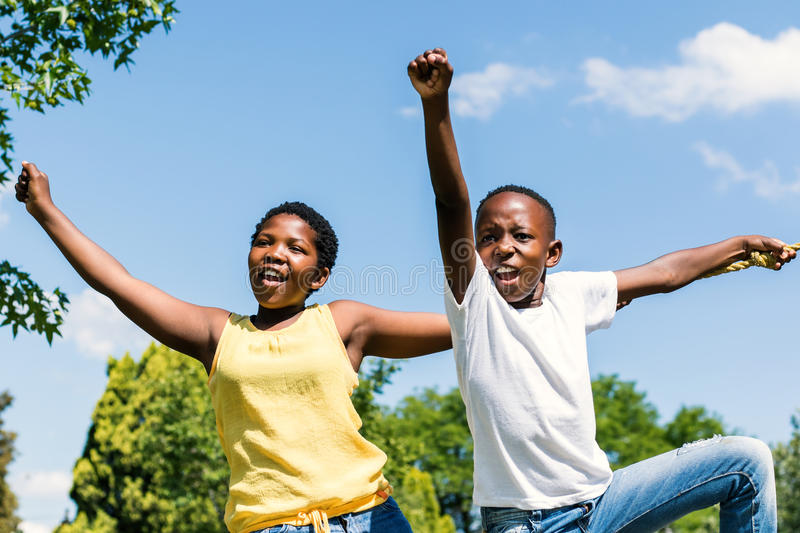 African Kids raising hands and shouting in park. stock photo