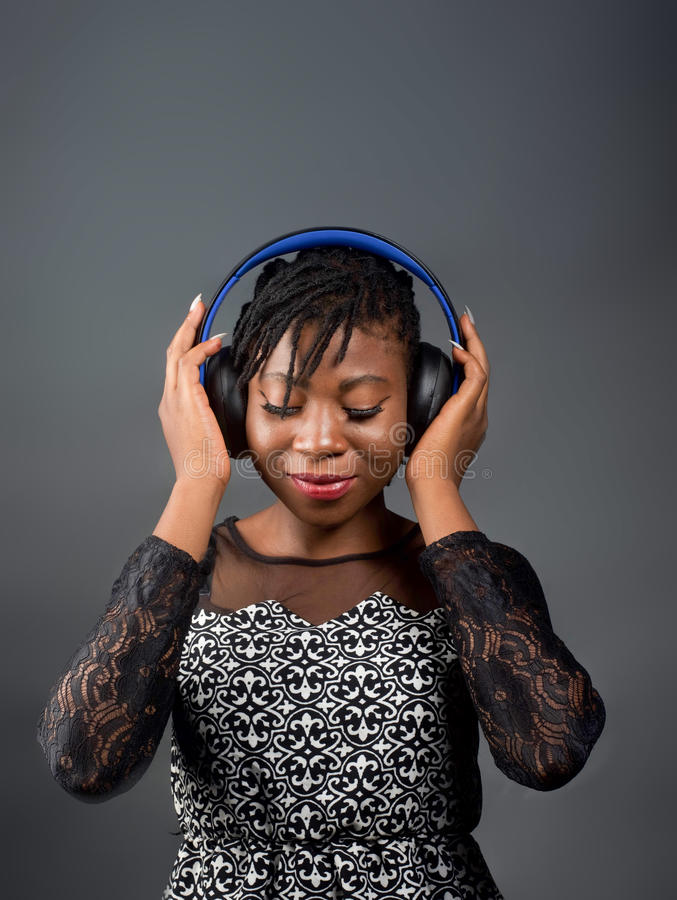 African lady listening to music. African lady listening ro music with wireless headphones stock image