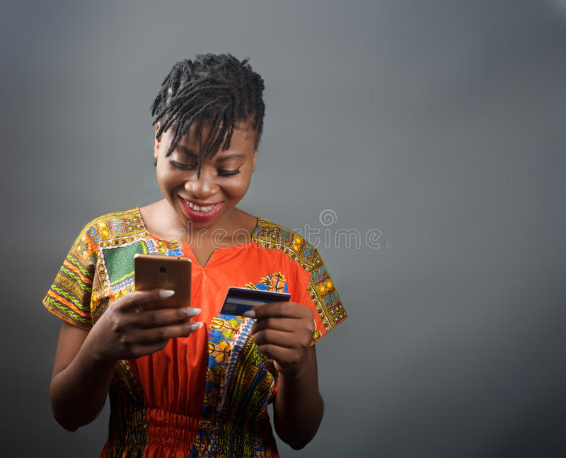 An african lady making an online payment with a debit card. An portrait shot of a lady making an online payment using a debit card royalty free stock photos