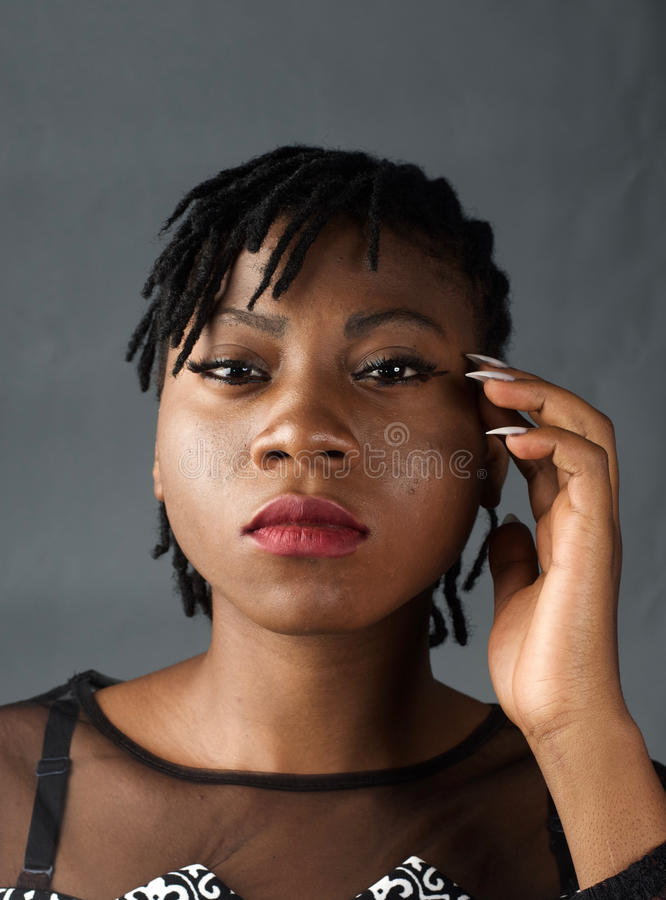 African lady with a serious look. A portrait shot of an African lady with a straight face royalty free stock photography