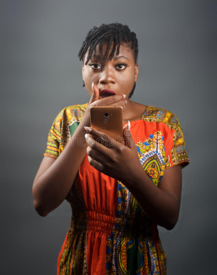 An african lady shocked at a message on her mobile phone. A portrait of an african woman who`s just received a shocking message stock photography