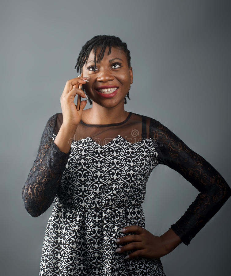 African lady smiling on a call. A portrait shot of an african lady receiving a phone call stock images