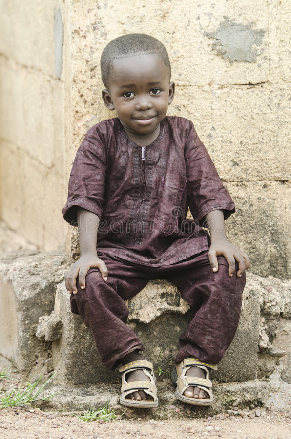 African little black boy sitting outdoors with a light smile royalty free stock image
