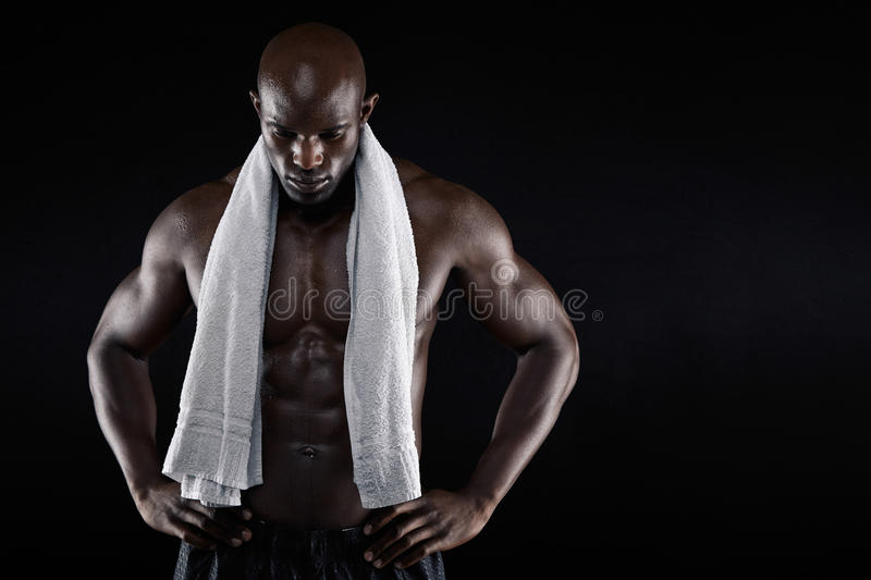 African male athlete after workout. Portrait of african male athlete after workout against black background. Shirtless muscular man with a towel looking down stock photos