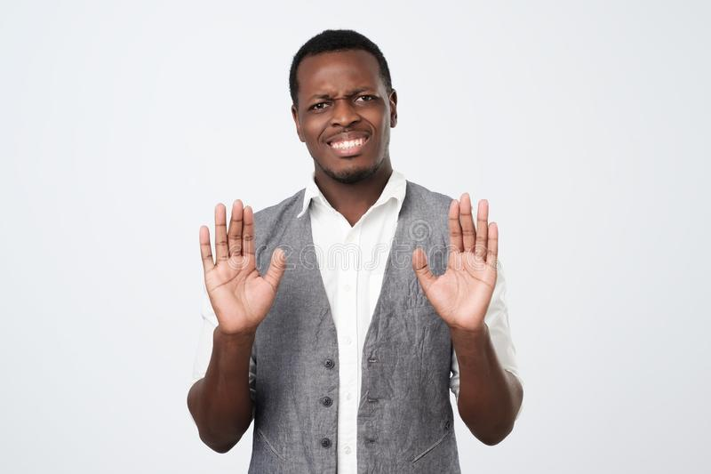 African male showing refusal gesture, like saying leave me in piece, has angry expression, poses against white studio. Attractive african male showing refusal royalty free stock photography