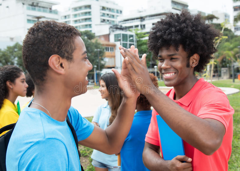 African male student give high five to indian student. Outdoor on campus of university royalty free stock photography