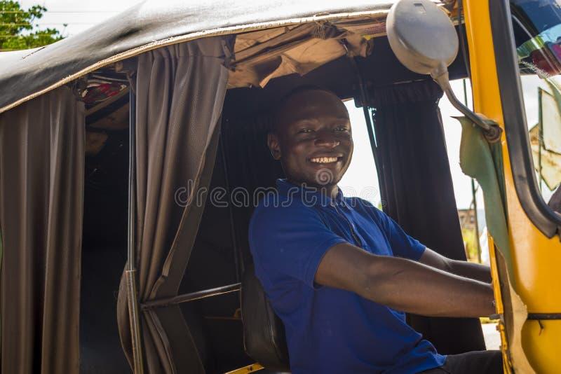 african man driving a tuk tuk taxi smiling stock photo