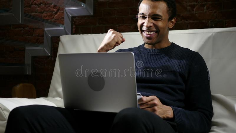 African Man Excited for Successful Online Shopping stock image
