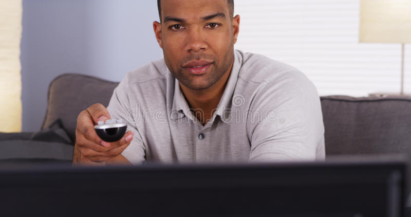 African man flipping through channels on TV. Man flipping through channels on TV royalty free stock images