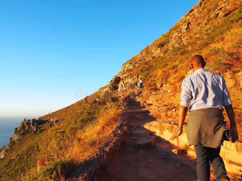African man hiking to on top of mountain royalty free stock photos