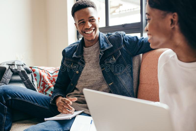 Students studying in campus building. African men with his classmate at college campus. Two young people doing class assignment at campus building stock image