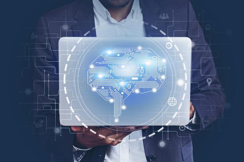 African man with laptop, AI brain hologram royalty free stock photography