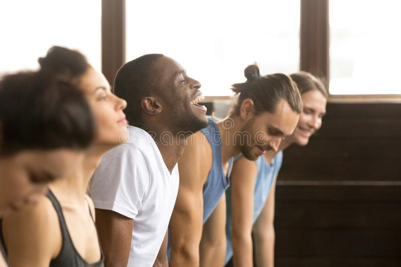 African man laughing doing yoga or plank at group training. African men beginner laughing having fun trying to do yoga pose, push ups plank or stretching in royalty free stock photo