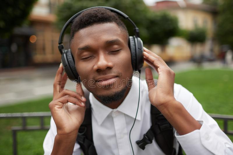 African man listening music in headphones with closed eyes and dreaming. royalty free stock photography