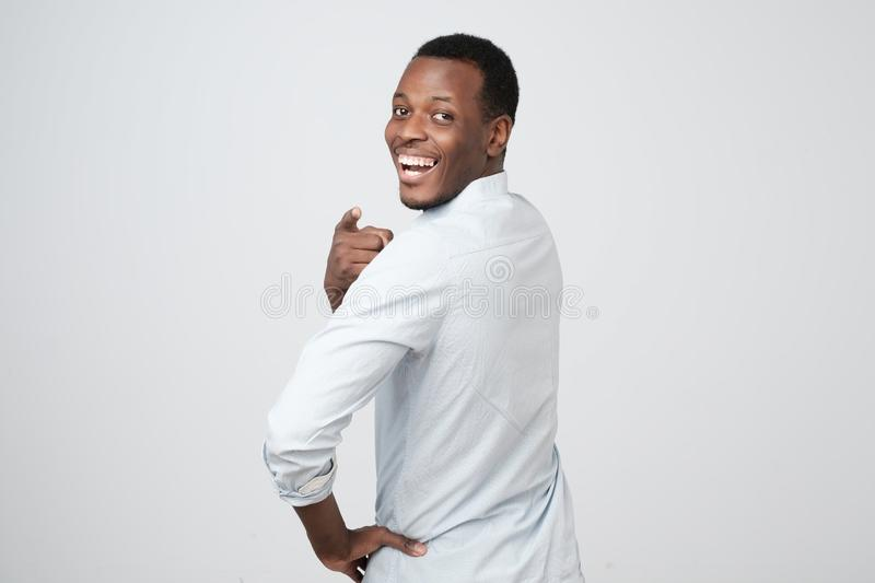 African man looking with happy smile in camera turning back and pointing with finger at camera. Back view of attractive african man looking with happy smile in stock photos