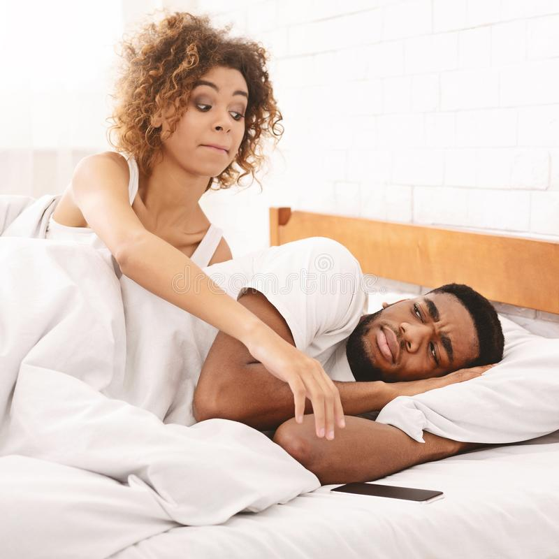 African man looking at his suspicious wife trying to check his cellphone in bed royalty free stock photos