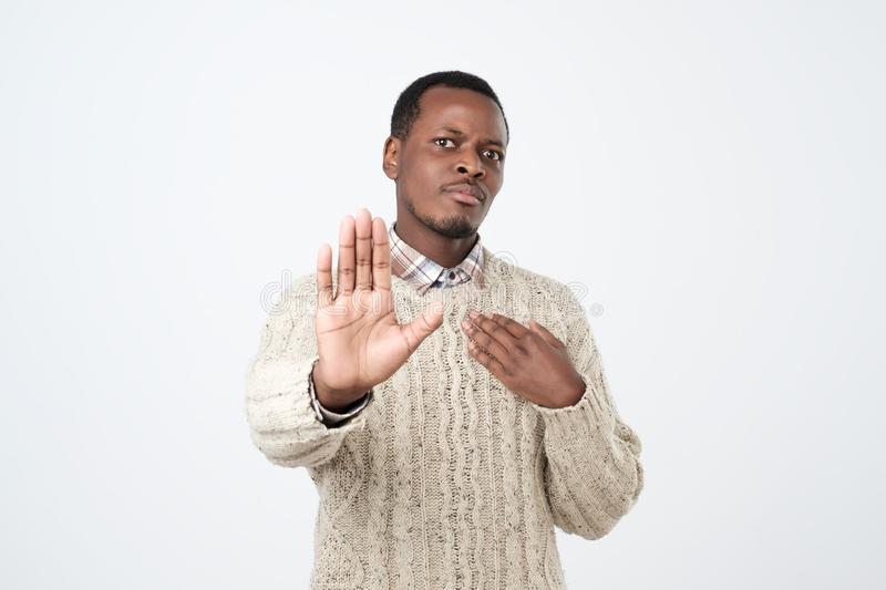 African man makes stop gesture, rejects something. African American man refuses drink alcohol,. People and disagreement concept. African man makes stop gesture royalty free stock image
