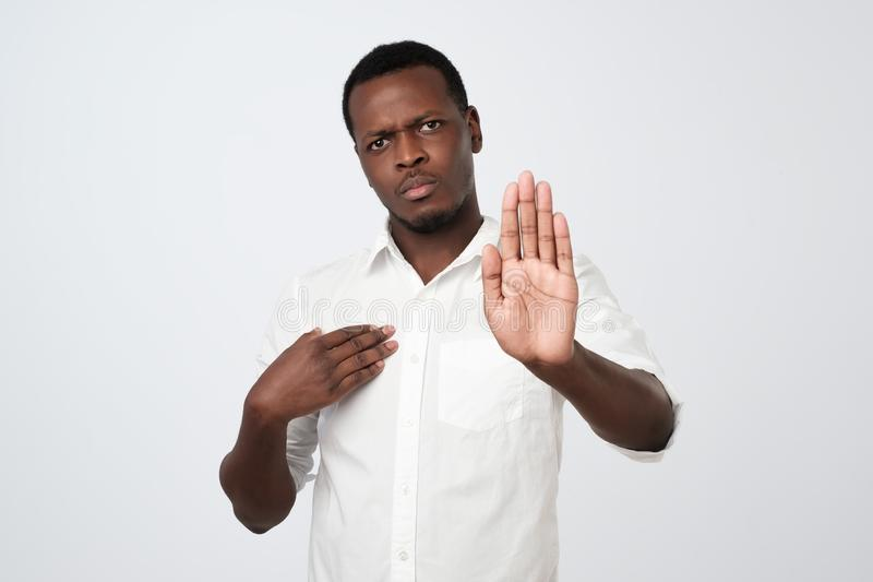 African man makes stop gesture, rejects something. African American man refuses drink alcohol,. People and disagreement concept. African man makes stop gesture stock photos