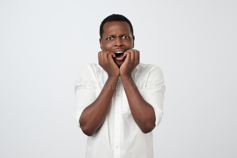 African man with nervous expression, bites finger nails, worries before interview. African man in white shirt with nervous expression, bites finger nails stock image