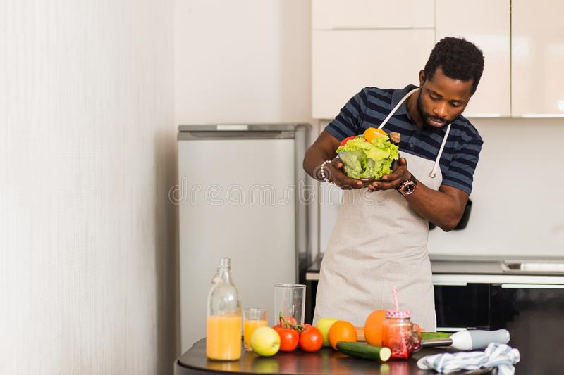 African man preparing healthy food at home in kitchen stock photography