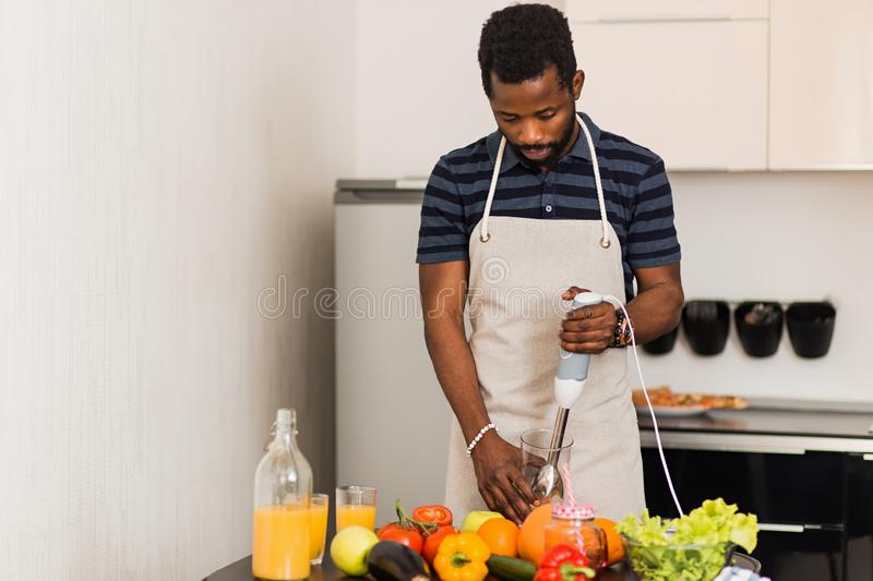African man preparing healthy food at home in kitchen royalty free stock photo