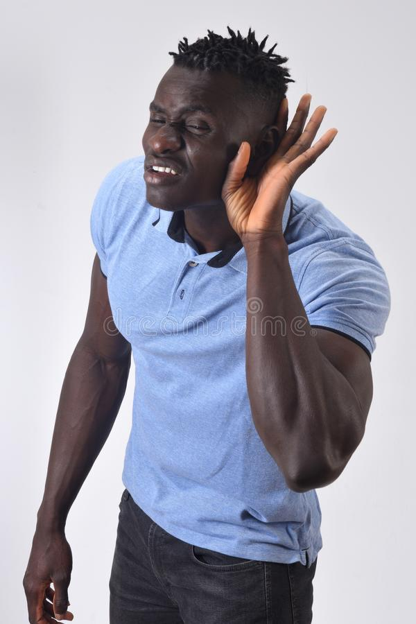 African man putting a hand on her ear because she can not hear on white background royalty free stock photos