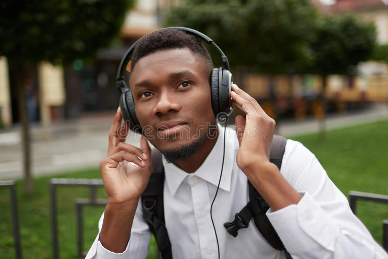African man resting outdoors and listening music. stock photo