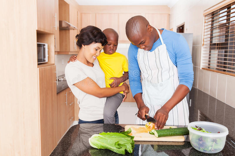 African man salad family. African men making salad for family in home kitchen stock photography