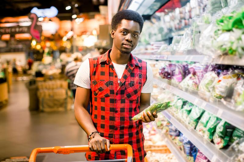 African man shopping in vegetable section at supermarket. Black man doing shopping at market while buying vegetables royalty free stock images