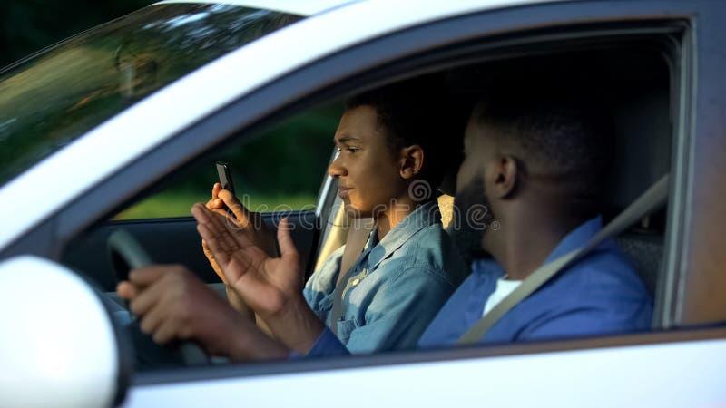 African man shouting at teenage son scrolling smartphone sitting car, behavior royalty free stock photos