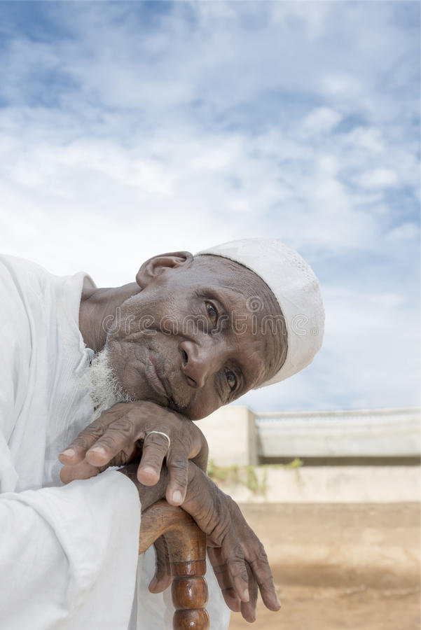 African man sitting in front of his house, eighty years old royalty free stock images