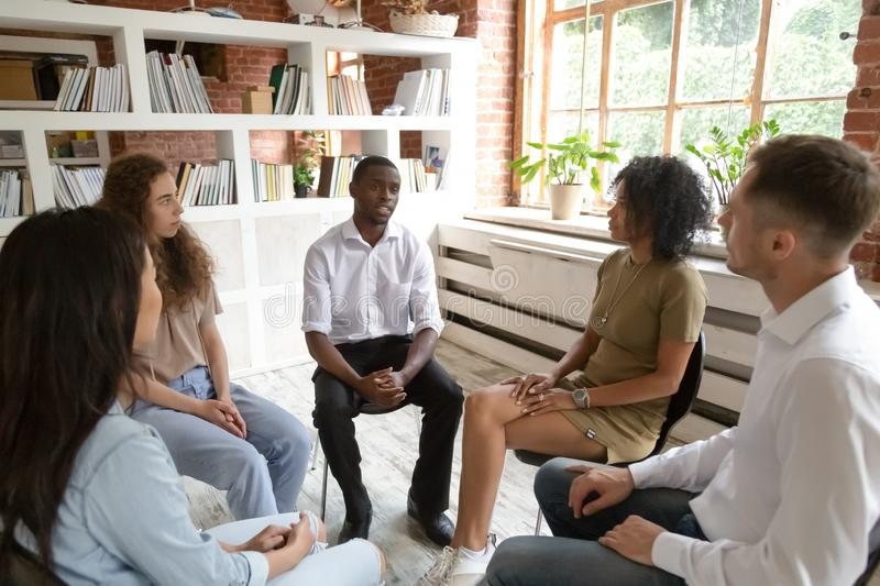 African man speaking during group counseling therapy session. African men speaking at group counseling therapy session looking for support in addiction treatment stock photo