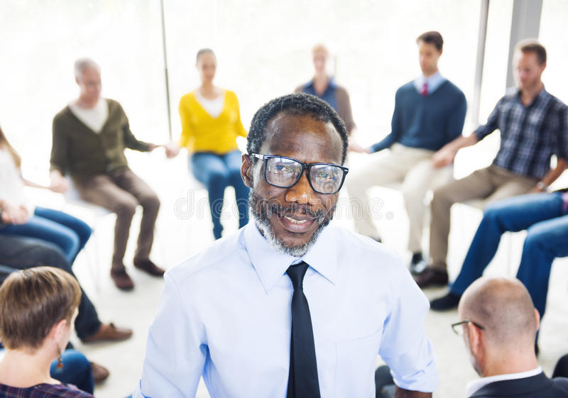 African Man Standing in Front of a Support Group royalty free stock photography
